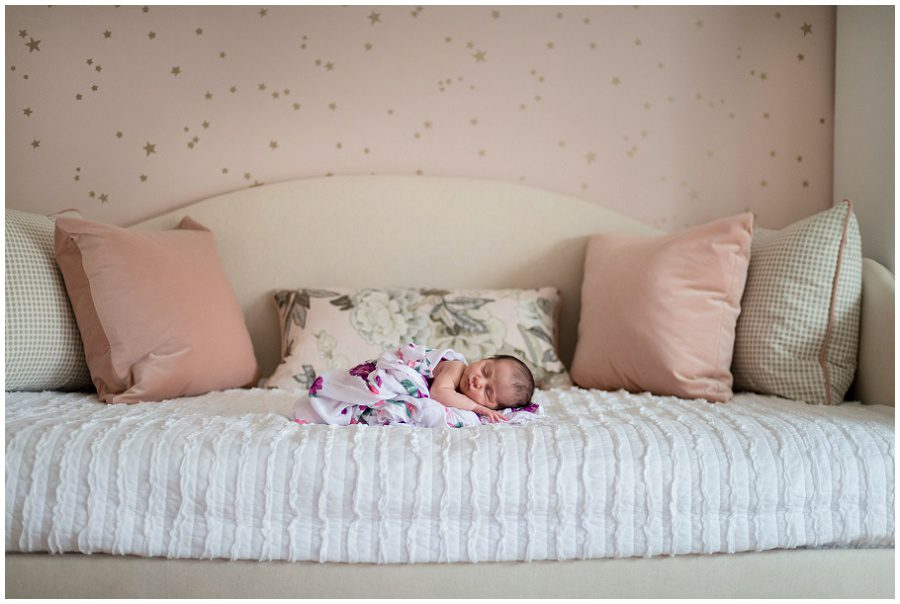 Newborn girl is lying on her daybed surrounded by pink pillows and in a pink wrap