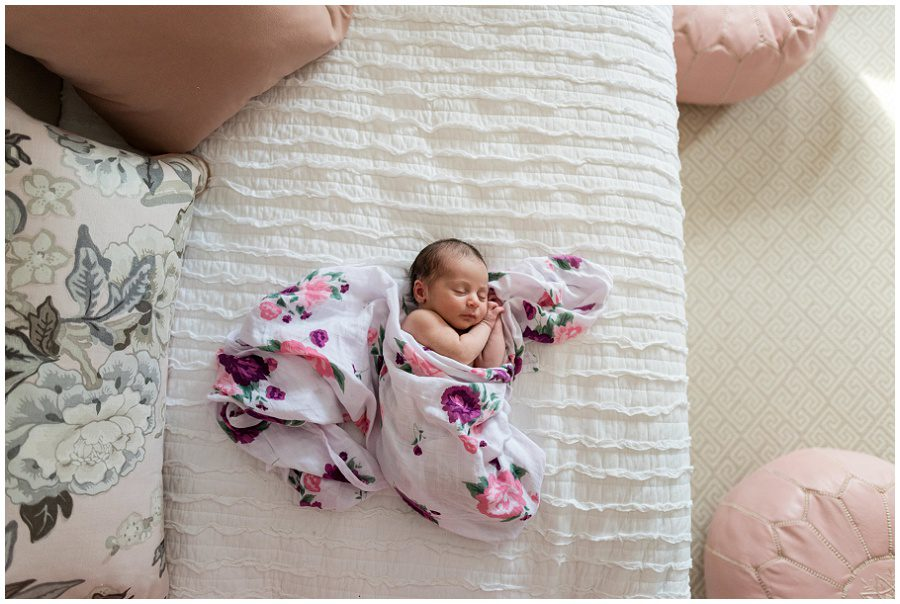 Newborn baby girl is lying on a day bed photographed from above looking down in her nursery.