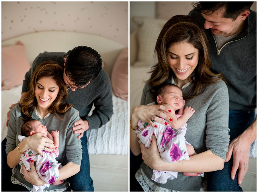 mother holding baby in home session on pink backless chairs vertical to parents holding sleeping newborn swaddled in blanket being embraced by father and smiling