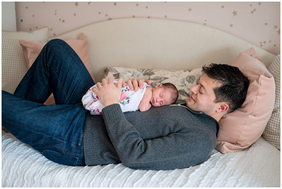 Father lying on day bed with newborn on chest as he looks down at baby that is swaddled in a white wrap