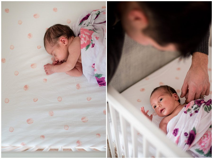 Newborn sleeping in her crib while wrapped in a swaddle. father is holding newborn's hand.