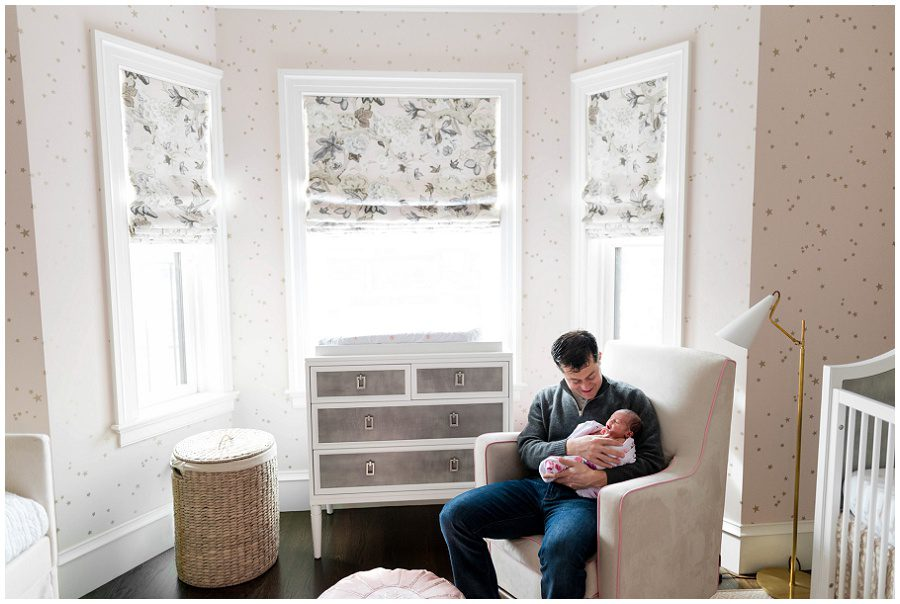 Father sits in a rocking chair while smiling at his newborn baby girl.