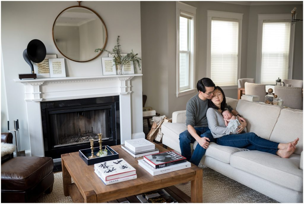 Newborn being held by parents in living room at home during lifestyle session in Cambridge