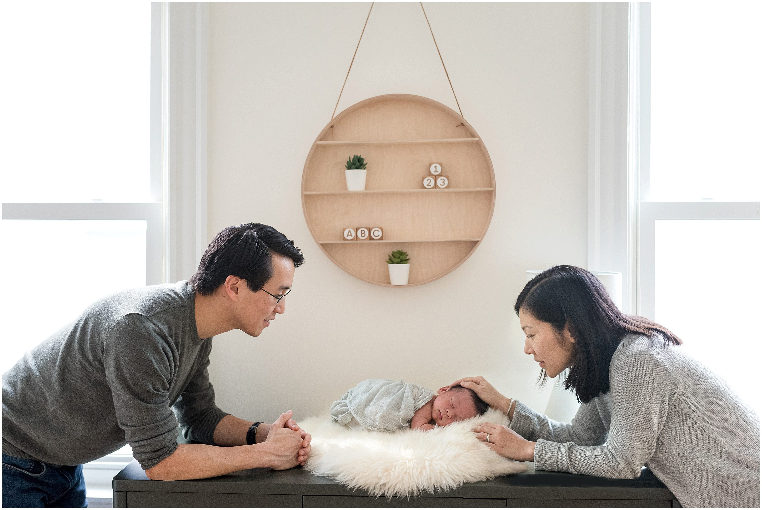 Newborn in his nursery being looked at by his mom and dad
