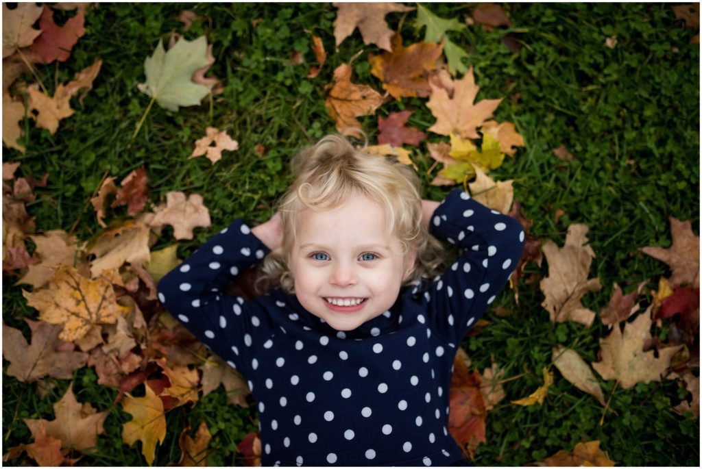 Child lying in leaves on ground Boston family photographer Fall foliage Larz Anderson
