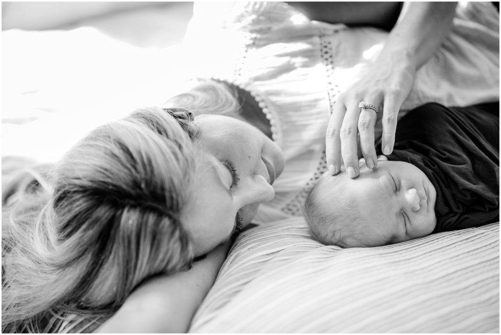 mother stroking son's hair during newborn session