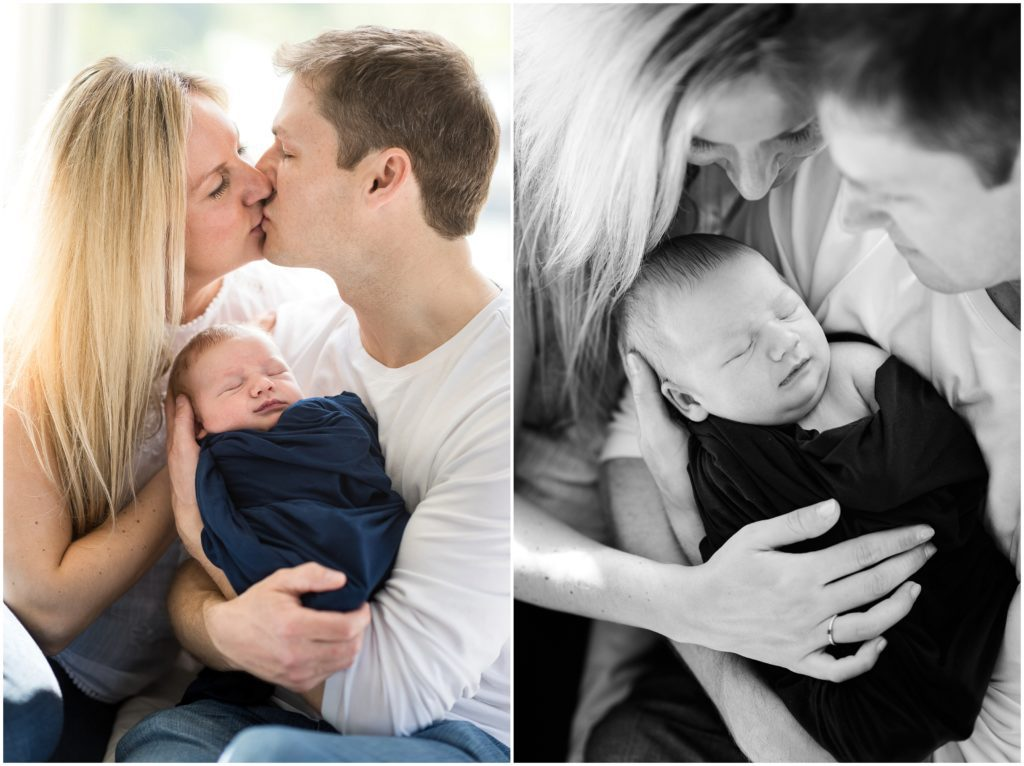 parents holding baby boy on bed kissing