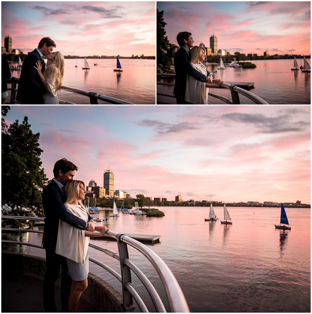 Sunset over the Charles River with boats in the background and city skyline, the couple in the foregraound