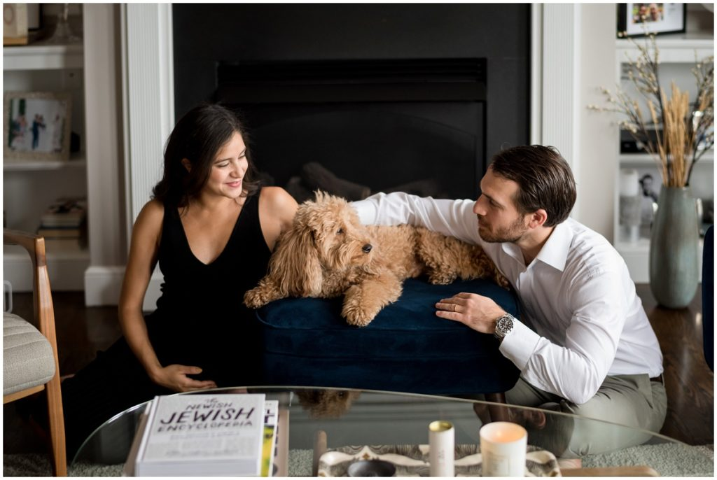 snuggling their puppy at home in front of fireplace during maternity session