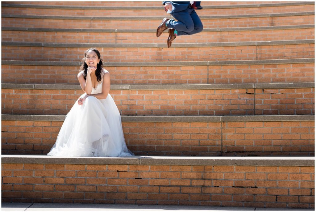 Groom jumping while bride poses in MIT