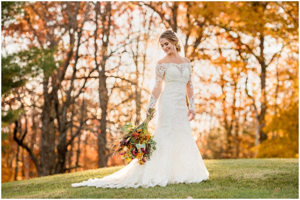 Bride against autumn trees outdoors in NH