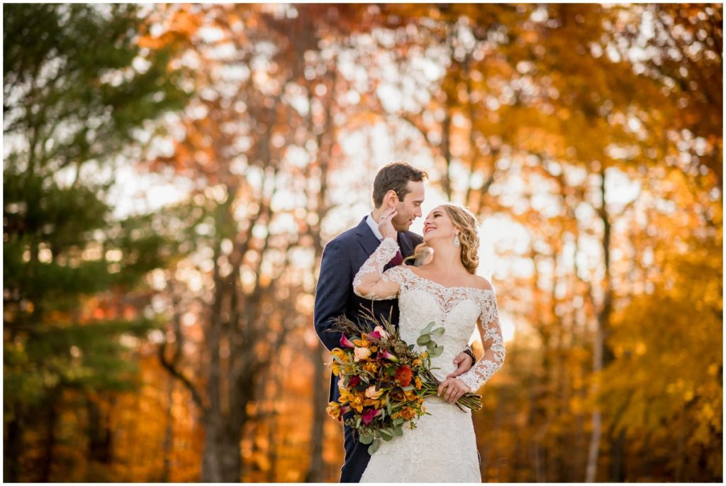 Bride and groom against orange fall leaves outdoors after wedding ceremony portraits