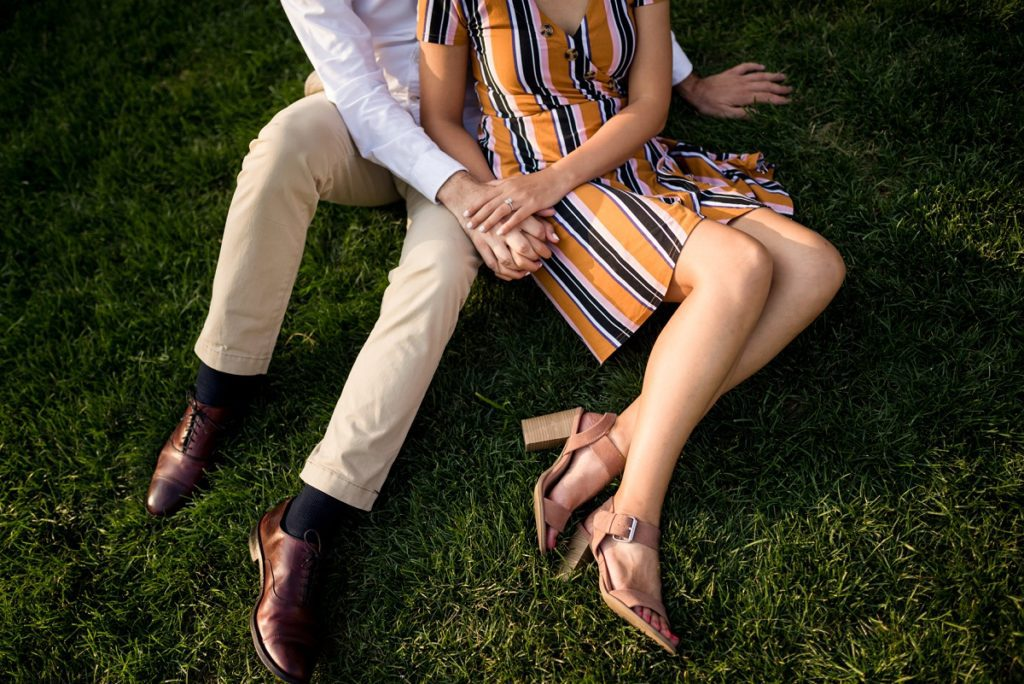 Couple holding hands on grass during engagement session
