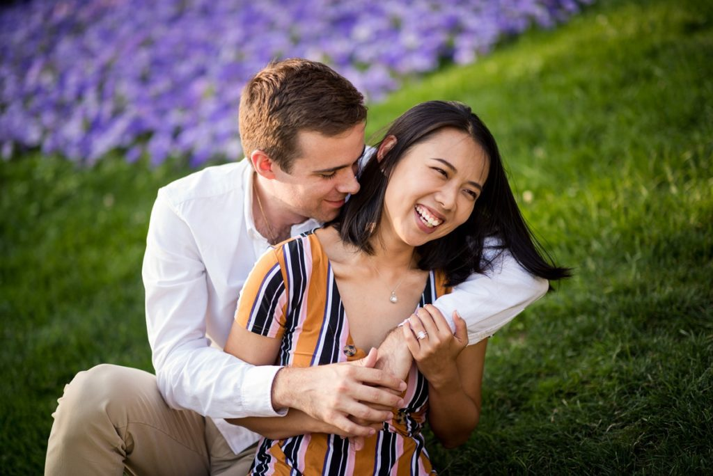 Fiancee smiling while being hugged by fiance on Cambridge City hall lawn