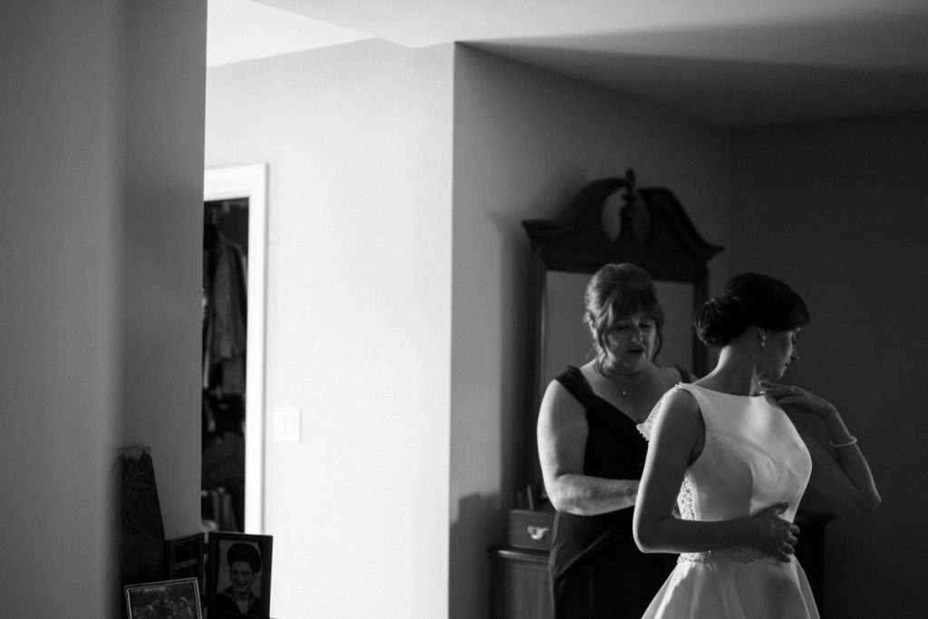 mother doing the back of the bride's dress in black and white image