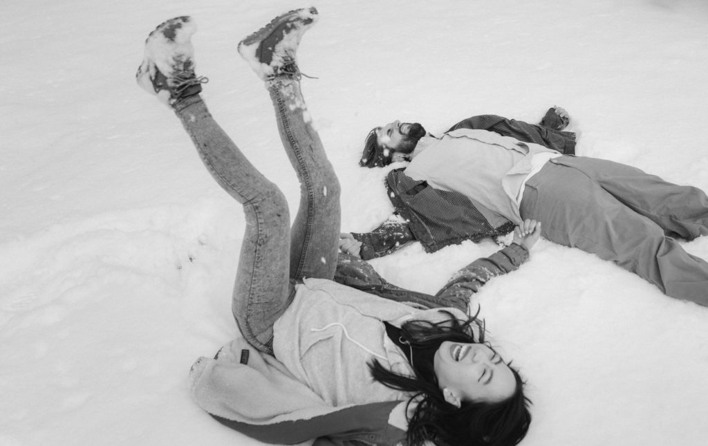 Couple lying in the snow together in Winter snow engagement