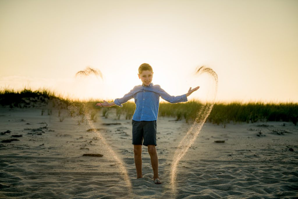Child throwing sand during sunset Cape Cod Family Pictures
